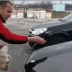 Man washes SUV with a cat