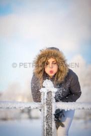Nuori nainen puhaltaa lunta