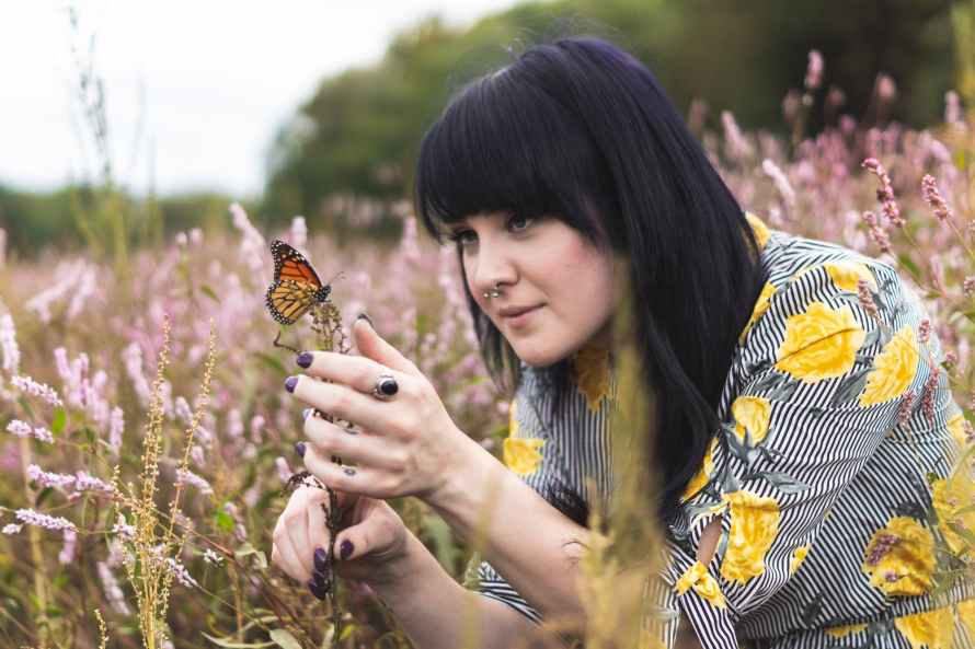 photo of woman holding butterfly