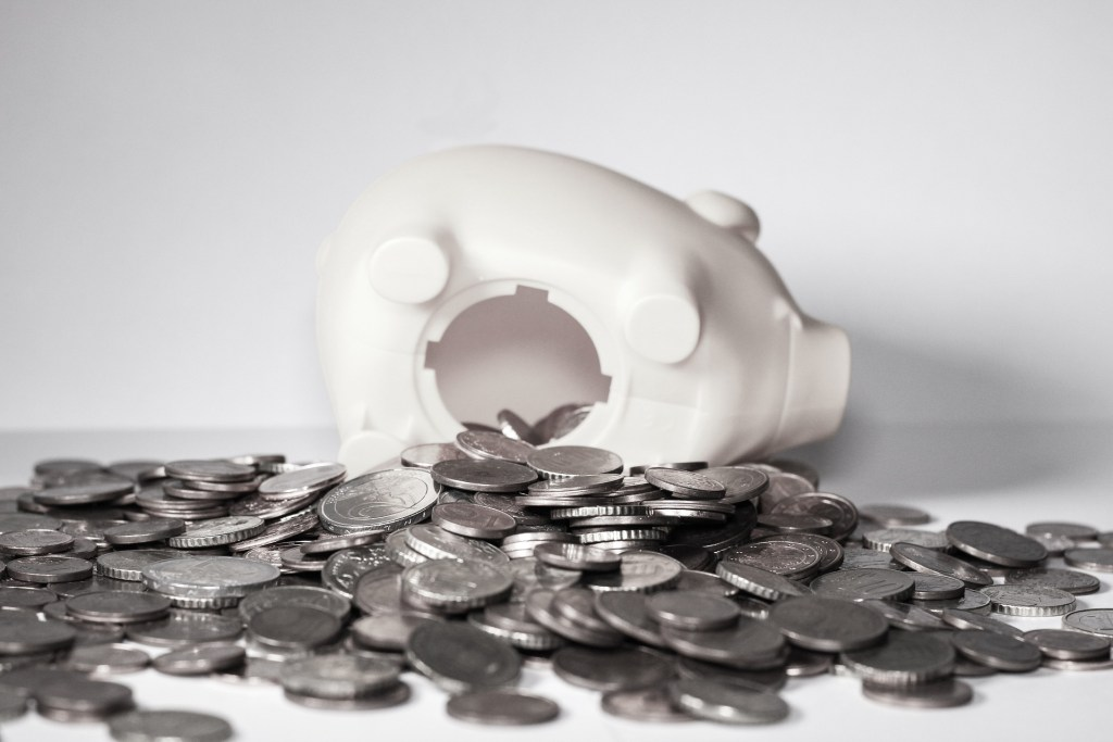 Budgeting Tips Piggy Bank tipped over with coins spilling out