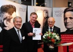 Caritas-Vorstand Klaus Weißbach (links) und Caritasdirektor Prälat Hans Lindenberger (rechts) gratulieren Christian Springer zur Auszeichnung. (Bild: Caritas)