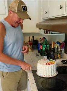 McKrae cuts his rainbow Pride cake