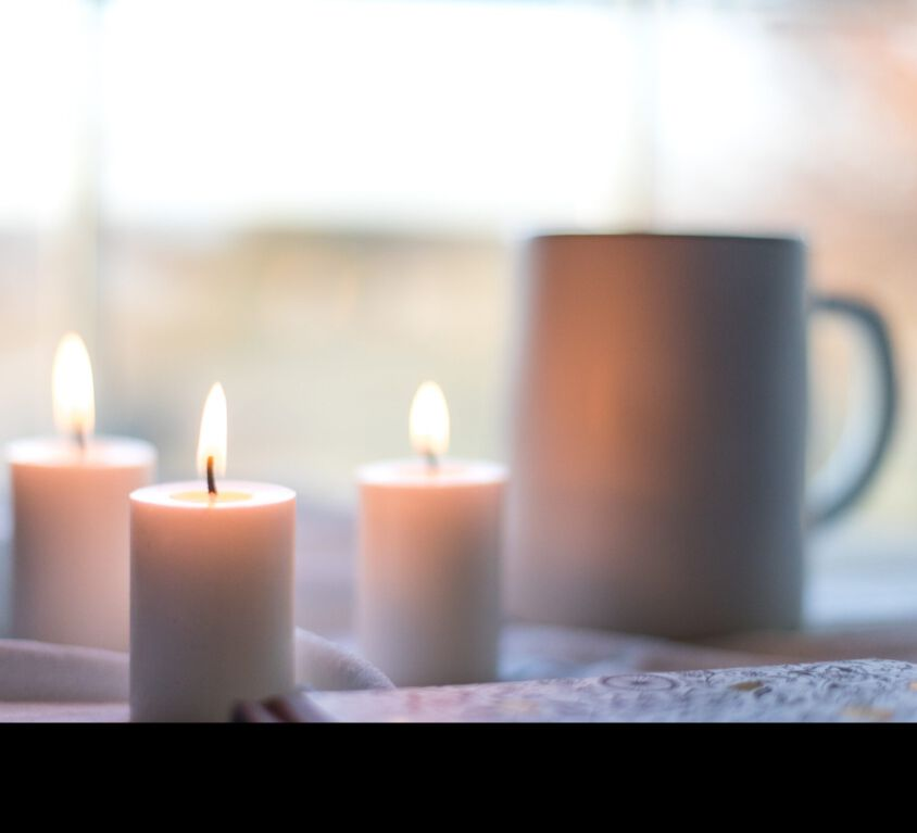 white pillar candles on white table