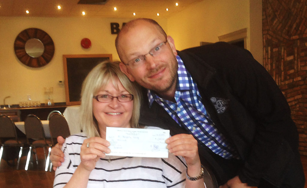 Prince George Kiwanis Club past president Corey Naphtali presents Marlene Yeomans, representing the Prince George Therapeutic Riding Association, with $1,000. The money was raised at the Kiwanis Club's Alefest in January.