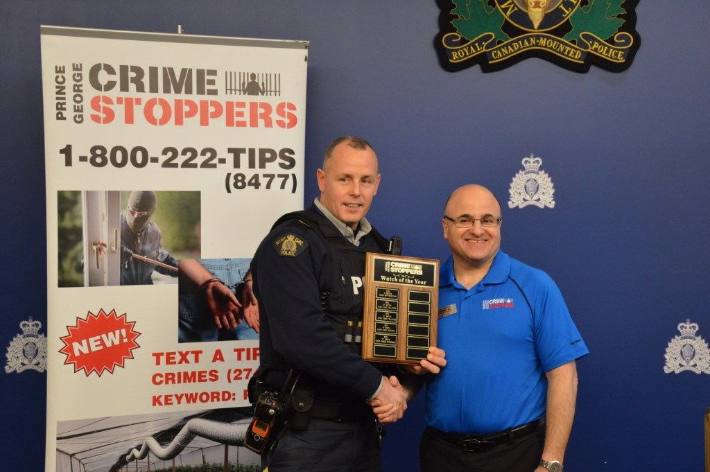 Cpl. Peter Rauliuk accepting the Watch of the Year award from Prince George Crime Stoppers president Ron Polillo.