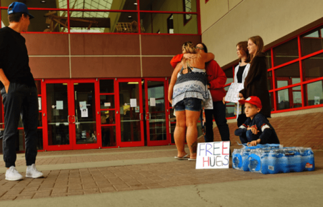 Orin Couston of Prince George, his sisters Emily and Grace, and his mom Samantha set up outside of the Emergency Reception Centre at the College of New Caledonia on Wednesday, giving Cariboo wildfire evacuees bottles of water - and free hugs. City of Prince George photo