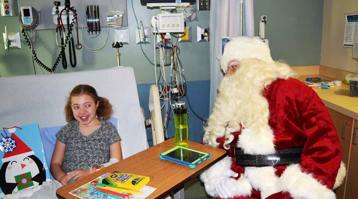 """Laurel Taylor, 11, gets a visit from Santa Claus in the pediatrics ward at the University Hospital of Northern B.C. Wednesday. """"He's funny,"""" Laurel said of the Big Guy. Bill Phillips photo"""