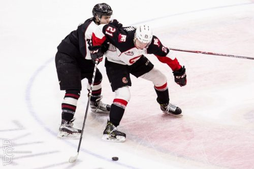 Jared Bethune gets checked against the Giants. Photo courtesy of the Prince George Cougars