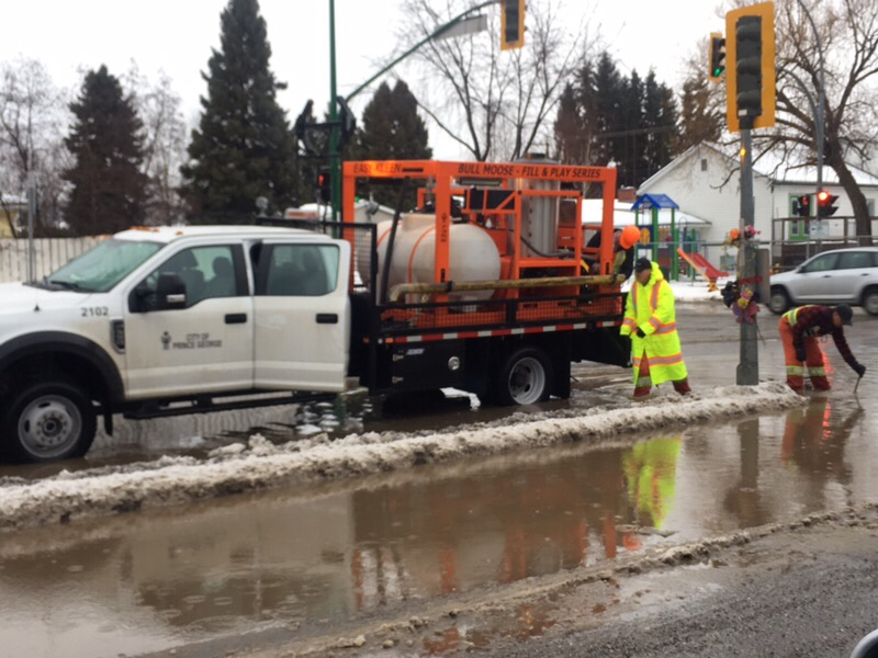 City crews work to drain water gathering at the intersection of 15th Avenue and Carney Street Monday afternoon.