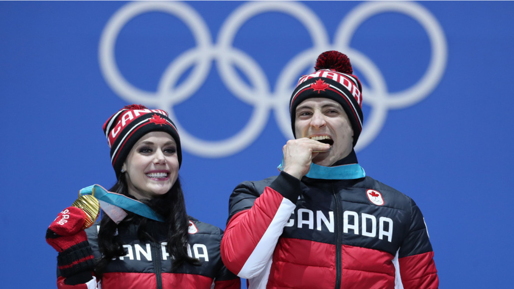 Skaters Tessa Virtue and Scott Moir show off the gold medals they won in ice dance at the PyeongChang Olympics. Canada Olympic Committee