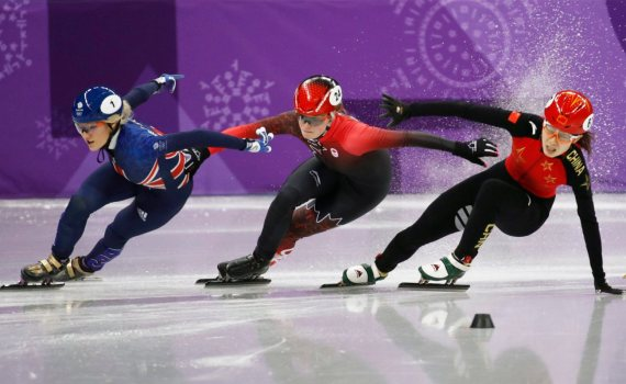 Qu Chunyu, right, of China crashes as Elise Christie, left, of Britain and Kim Boutin of Canada skate past during their ladies' 500 meters short track speedskating semifinal in the Gangneung Ice Arena at the 2018 Winter Olympics in Gangneung, South Korea, Tuesday, Feb. 13, 2018. (AP Photo/Patrick Semansky)