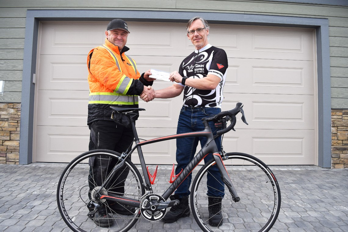 Davor Drazenovic of Portal Installations presents Wheelin' Warriors team member Dan Gall with $1,000 towards his Ride to Cure Cancer in August. Bill Phillips photo