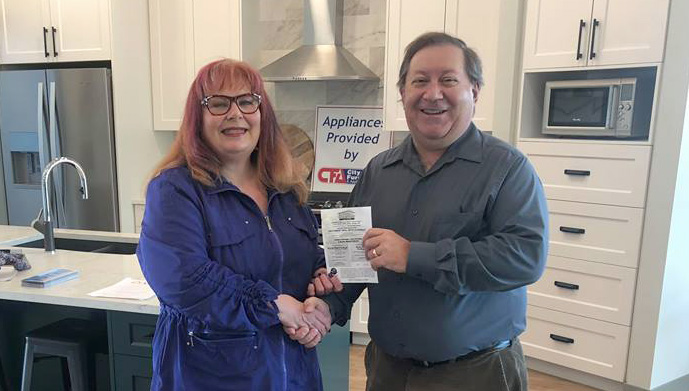 Prince George Daily News publisher Bill Phillips presents Heather MacIntosh with a Hospice Dream Home Lottery ticket. MacIntosh was the lucky winner of the PG Daily News' recent Facebook contest for a ticket on home in the Nechako View Subdivision.