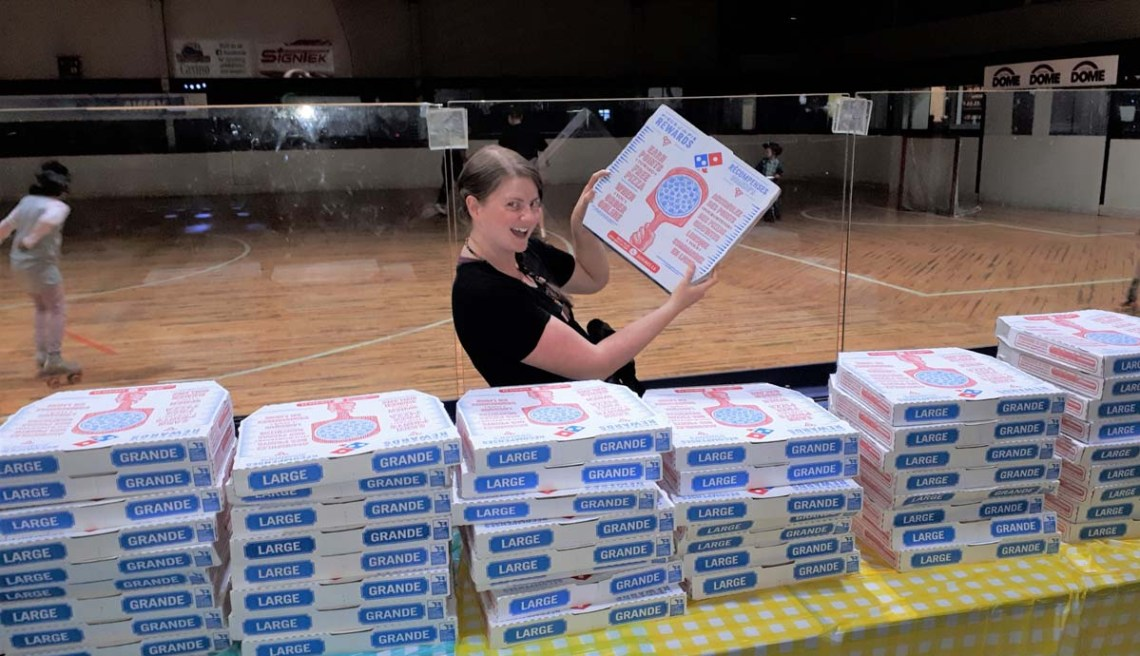Kris Holland, a School District No. 57 Youth Care Worker, gets ready to serve up a mountain of pizza at the Strengthening Families Program wrap-up party at the PG Dome. School District 57 photo