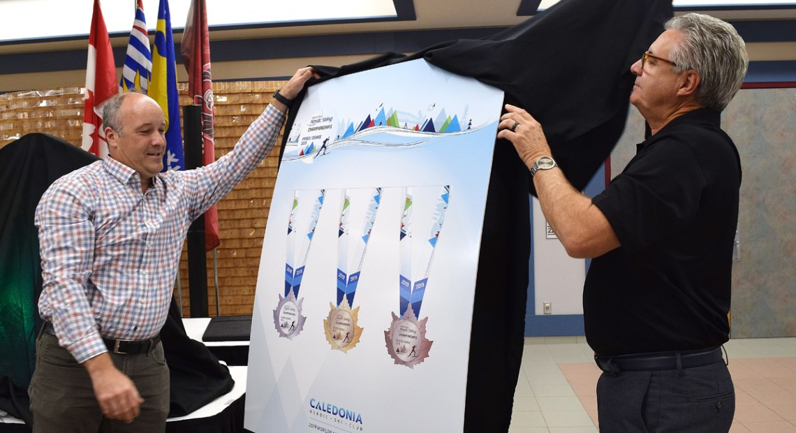 Kevin Pettersen, 2019 World Para Nordic Championships Local Organizing Committee chair, and Mayor Lyn Hall unveil the medals that will be won during the championships this winter. Bill Phillips photo