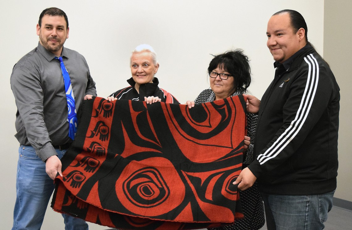 Lheidli T'enneh Chief Clay Pountney, along with band councillors Helen Buzas and Josh Seymour, present Penelope Harris with a Lheidli T'enneh blanket and jacket in appreciation of her gifting two parcels of land to the band. Bill Phillips photo