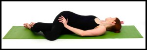 Woman does twist yoga pose.