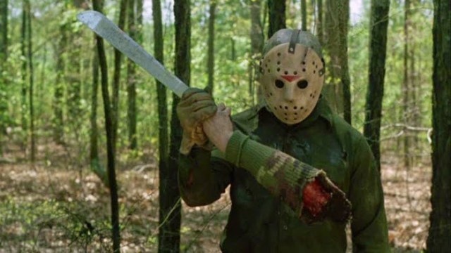 Jason Voorhees wears his classic hockey mask while holding a machete that has an arm still attached.