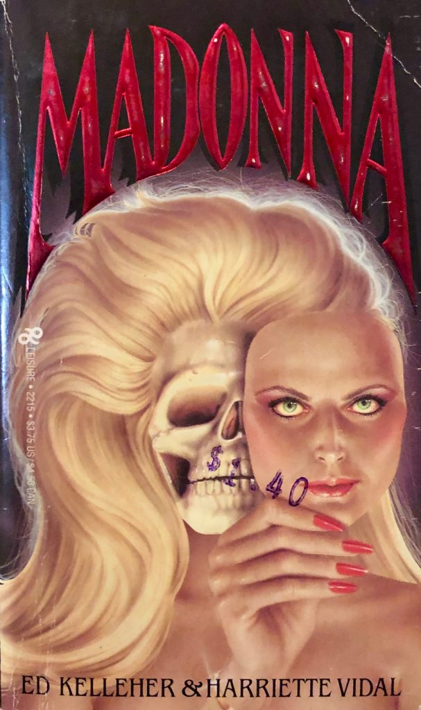"""Front cover of the horror paperback """"Madonna,"""" featuring a beautiful blonde woman removing her face to reveal the skull underneath."""
