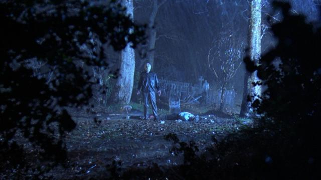 Jason Voorhees in the distance standing by an open grave.