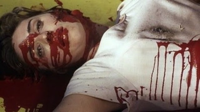 Close up of a woman in a white t-shirt. Her face and body are covered in blood from the Herschell Gordon Lewis Feast box set.