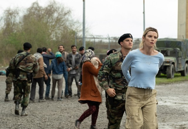 Soliders detain a group of immigrants in the background while another soldier walks holds a white woman's hands behind her back