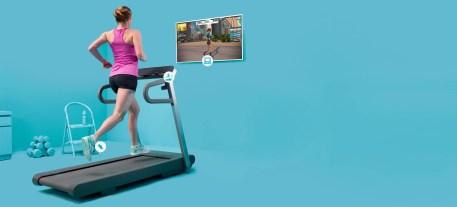 A runner on a treadmill in front of a screen displaying Zwift, which she is using to record her run