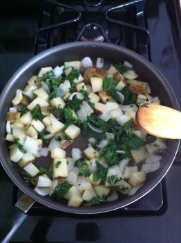 Potatoes, onions, and greens in the pan!