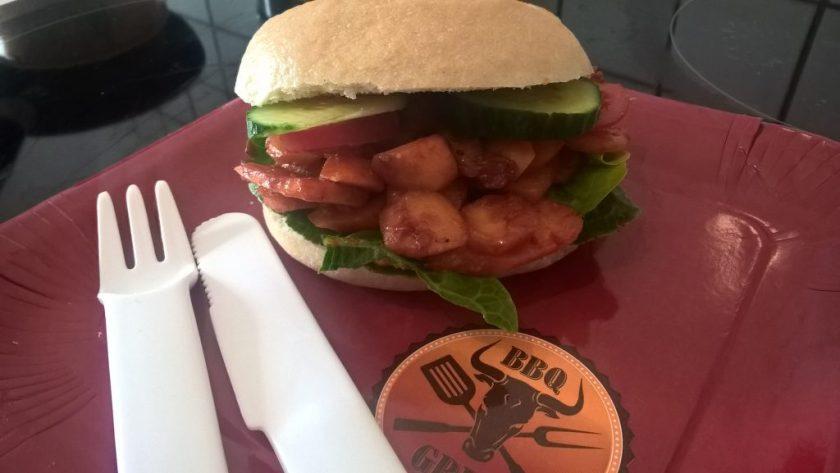 Ein Hamburger liegt auf einem Pappteller. Das Innenleben des Burgers besteht aus Möhren. Daneben liegt mehrfach verwendbares Plastikbesteck. Wenn man auf das Bild klickt gelangt man zum eiweißarmen Rezept für Menschen mit PKU.