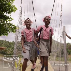 Two girls in school uniforms cross a bridge in Haiti.