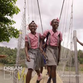 Two girls in school uniforms cross a bridge in Haiti.