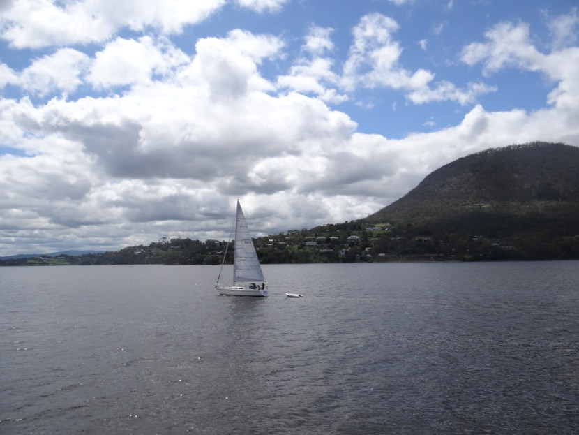 Sailing in Hobart, Tasmania on water with blue skies and puffy clouds