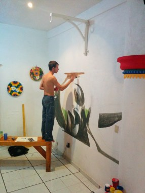Some guy painting a wall mural for free hostel bed and stay, which seems to be fairly common practice.