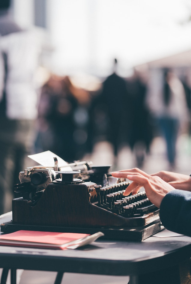 a typewriter with someone working on it