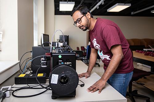 Student looking at 3D printer