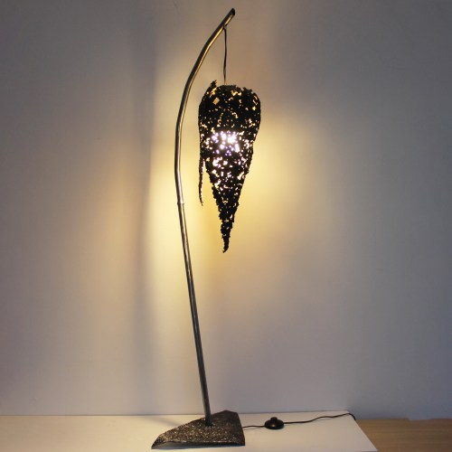 Lampadaire de salon design et art : une lampe sculpture unique en dentelle d'acier représentant une flamme suspendue.  La partie basse intérieure de la flamme est recouverte à la feuille d'or 24 carats pour rehausser l'éclat naturel de la lumière. Elle est équipée d'un système d'éclairage avec ampoule LED (12w - Norme C.E.). Livrée avec l'ampoule, et le système d'éclairage : prise et interrupteur. La base de ce lampadaire est en acier et lui confère une belle stabilité.  La sculpture flamme est suspendue au pied par un cable en acier. C'est une pièce unique, signée, qui est accompagnée de son certificat d'authenticité.  Base triangulaire 41 x 21,5