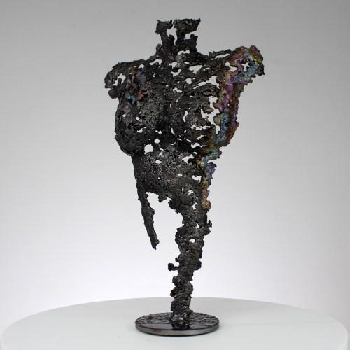 Sculpture représentant un corps de femme. Sculpture en dentelle de bronze, acier et pigments. Pour créer cette sculpture j'ai fait fondre au goutte à goutte le bronze et l'acier dans un moule en sable dans lequel j'ai modelé la forme.  J'ai ensuite chauffé le bronze et appliqué des pigments pour apporter des touches de couleurs. Socle en acier (diamètre 10 cm) La dentelle de métal permet de souligner les formes du corps de la femme, tout en jouant avec la lumière et la transparence. Cette sculpture est entièrement vernie pour conserver le même aspect. Pièce unique. Sculpture signée, et accompagnée de son certificat d'authenticité.  Hauteur 38 cm - Largeur 22 cm - Profondeur 11 cm