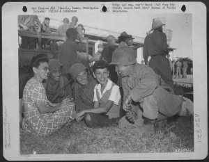 Liberated Los Banos internees talking with GIs 1945