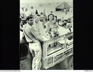 MANILA, THE PHILIPPINES, 1945. FORMER INTERNEES IN A TRUCK AT NICHOLLS FIELD AIRSTRIP PRIOR TO LEAVING FOR AUSTRALIA AFTER LIBERATION. FROM LEFT, ABE (SURNAME UNKNOWN) AND PAULA PRATT, WHO WERE ENGAGED TO BE MARRIED; MARIE PRESTON HOLDING PAM BUTTFIELD, WHO WAS BORN IN THE SANTO TOMAS UNIVERSITY INTERNMENT CAMP. (DONOR: B. COOPER).