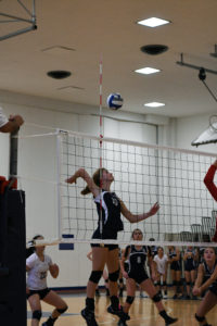 Captain Evelyn Mesler '17 leaps into the air for a spike.