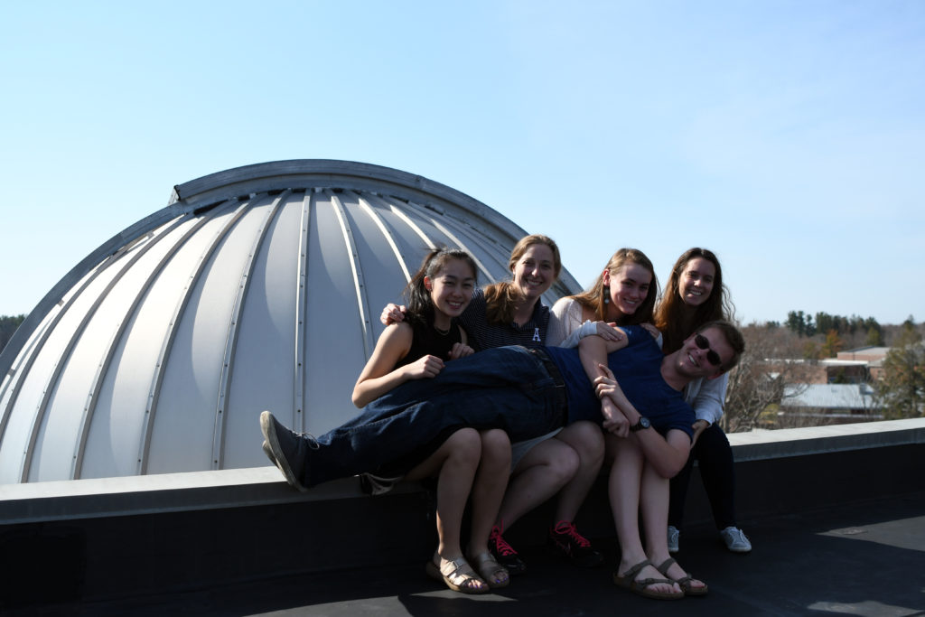 Kaitlin Hoang '17, Caroline Odden, Instructor in Physics and Astronomy, Paige Morss '17, Maria Caso '17, and Preston Dial '17 pose in front of the observatory.
