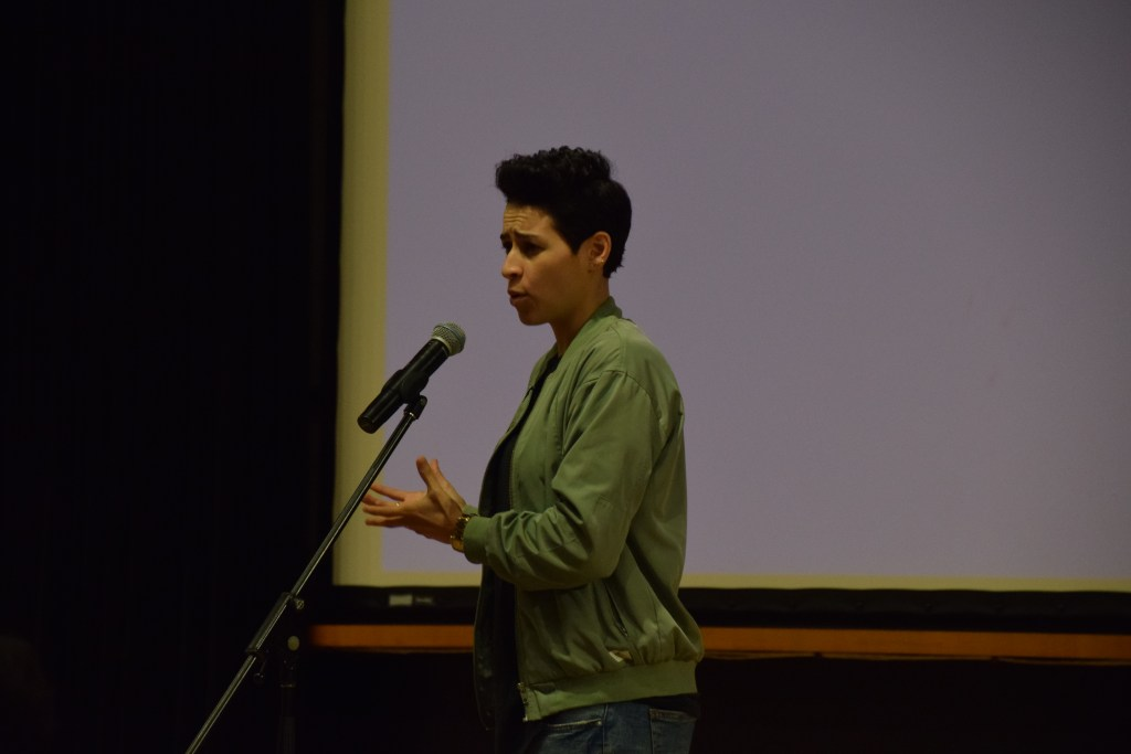 Denice Frohman gesticulates while performing. Her work often challenges questions of race, sexuality, and the relationship between the two.
