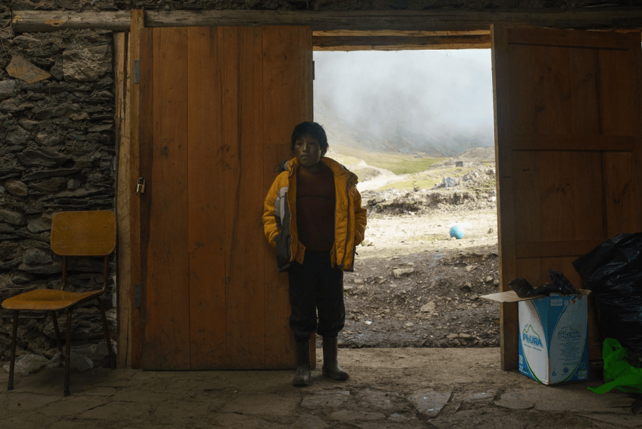 A Quechua boy stands in the doorway of the community center in his village, seven hours from the nearest city.