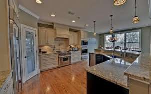 Inviting kitchen with white and dark cabinetry topped by granite.