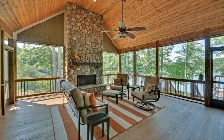 Screened in porch with a stone fireplace, great space to entertain.