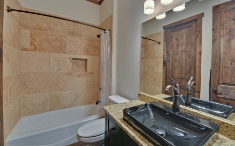 Guest bath with a tiled surround tub shower combo and a raised bowl vanity topped with granite.
