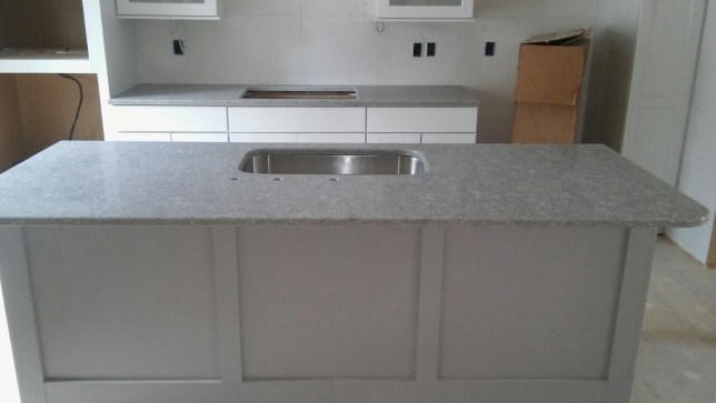 Kitchen island with white cabinetry and grey granite countertop.