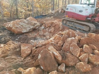 This shows the massive amount of large rocks that have been dug up from the building site.