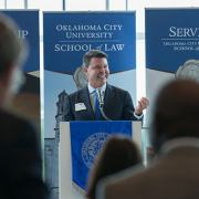 Jim Roth. Phillips Murrah Director and Oklahoma City University School of Law Dean, announces the revival of OCU Law's Alumni association at a meeting in early September.