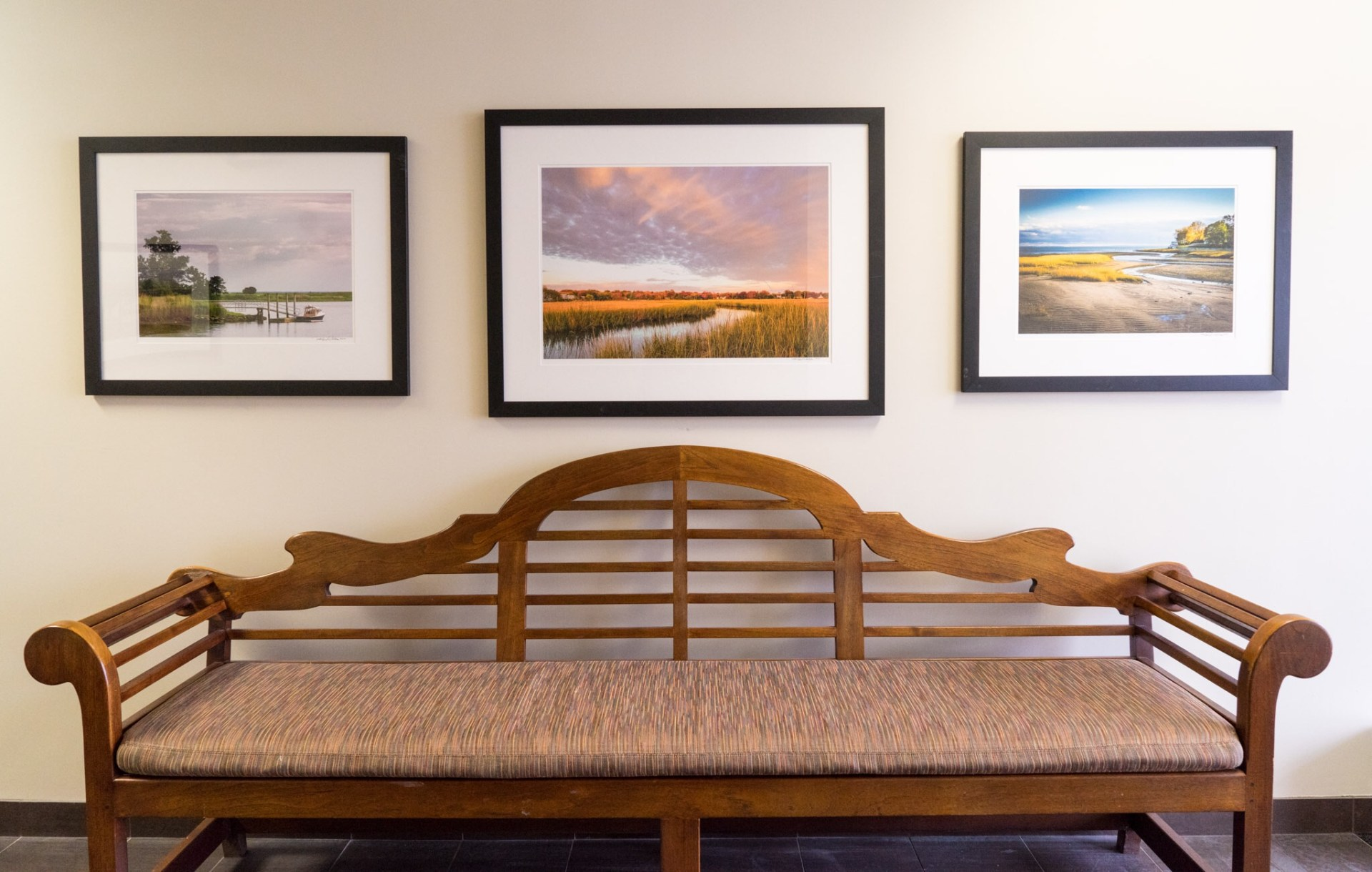 three framed images in front of bench